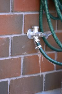 An exterior leaking water tap connected to a hose on bricks